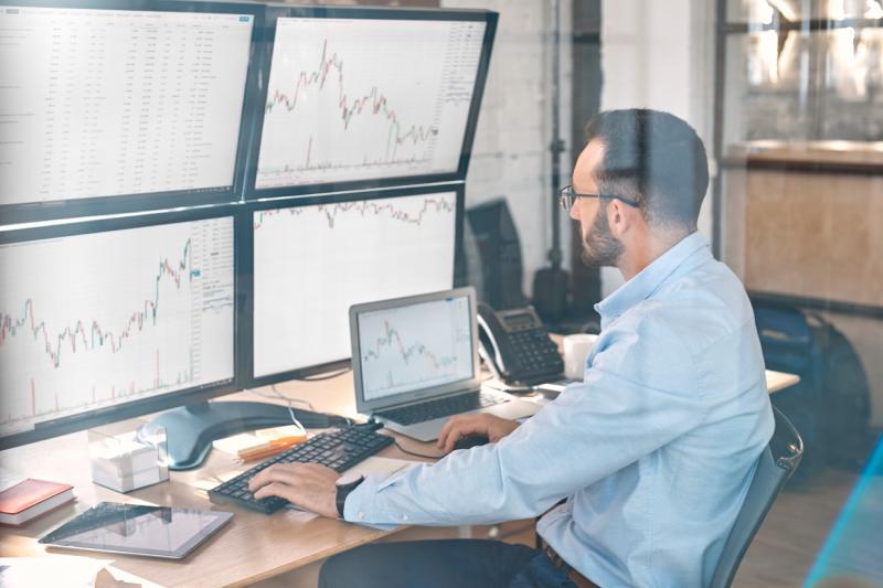 Trader at desk using multiple monitors