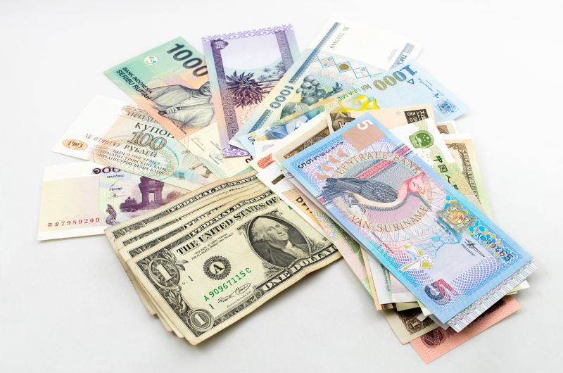 Different countries banknotes spread out flat on table