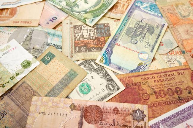 Exotic currency notes scattered on table