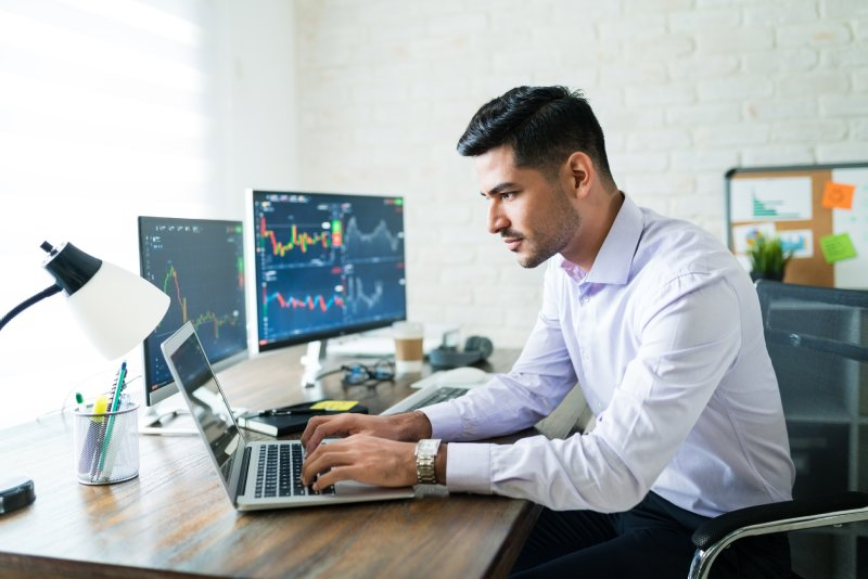 Man trading on his laptop and two monitors