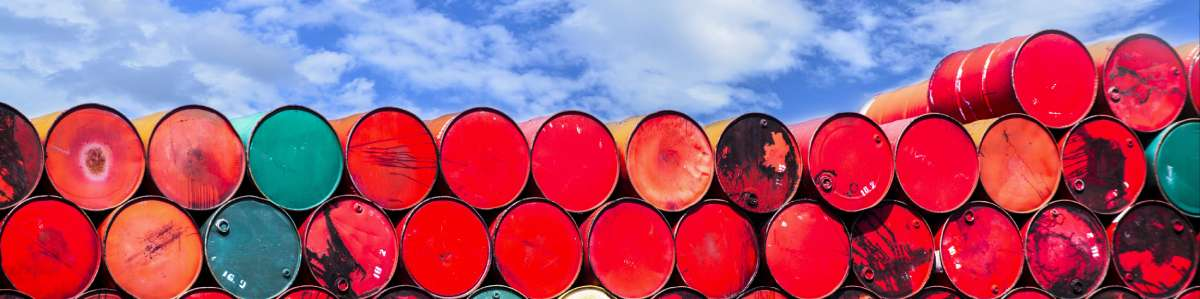 A wall of stacked red oil barrels
